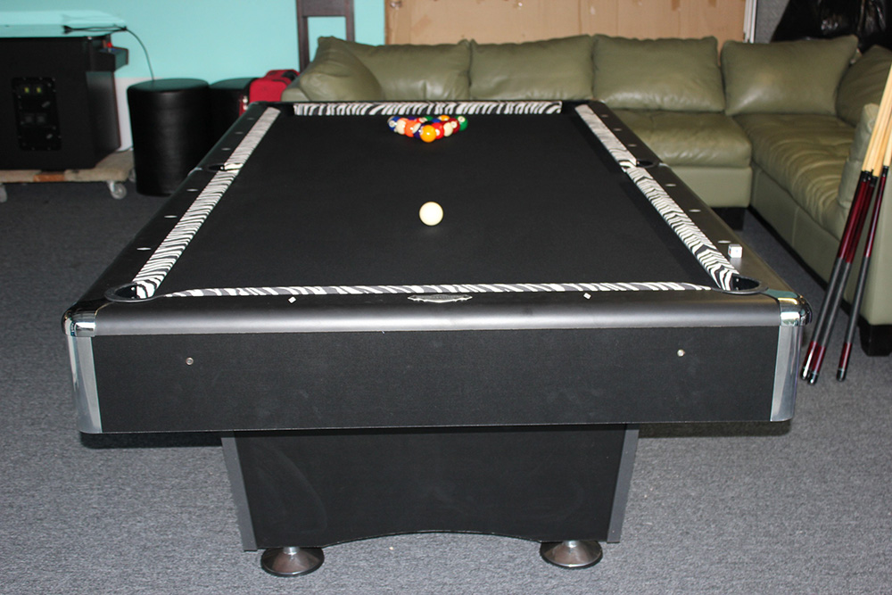 Black felt with Zebra skin printed cloth on the rails. Big pimpin', not too many tournaments will be played on this one.